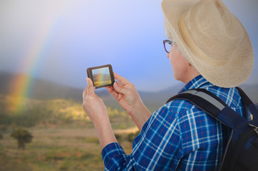 Hiking woman photographing rainbow