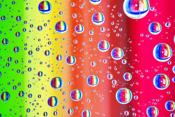 Colorful abstract background of water drops on glass with rainbow colors