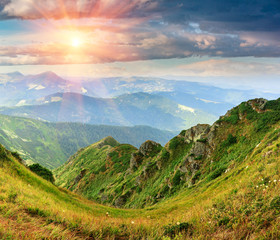 Beautiful colorful landscape of summer mountains. View of cliff tops and  green hills.