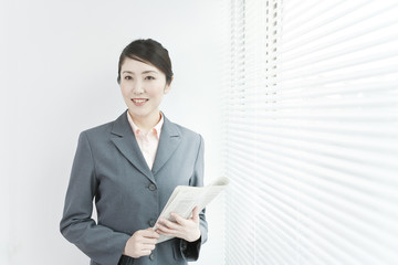 A business woman standing by windows