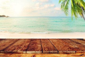 Top of wood table on blurred sea with coconut tree background - Empty ready for your product display montage. Concept of beach in summer. vintage color tone