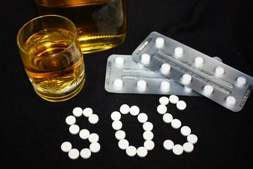 White pills on black background, which forming the word SOS, with glass and bottle of alcohol. Benzodiazepines suicide combination or addiction narcotic concept.