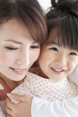 Woman embracing daughter, smiling, close up