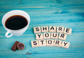 share your story. Coffee mug and wooden letters on wooden background.