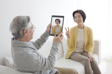 Senior couple taking photo with tablet PC