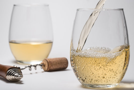 Pouring White Wine into Stemless Glasses