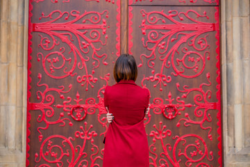 beautiful young woman hugging herself in front of the wonderful huge door in Poland