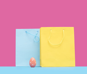 cool yellow and blue shopping bags and easter egg in front of the wonderful pink background