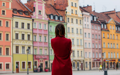 beautiful young woman hugging herself in front of the splendid view of street in Poland