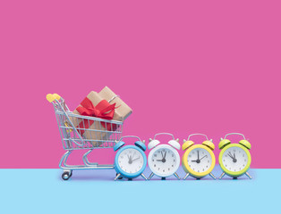 small gift in cool shopping cart and colorful alarm clocks in front of wonderful pink background