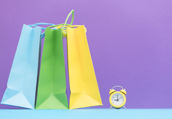 cute small alarm clock and shopping bags on the wonderful purple background