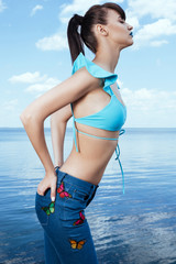 Girl in jeans with butterfly print and in swimwear top posing sexy on the seaside. Model sideways with hands in back pockets over the ocean and sky background