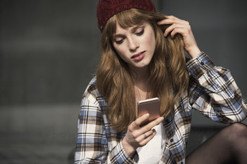 close up of a young woman that is using an application in her smartphone device to send a text message