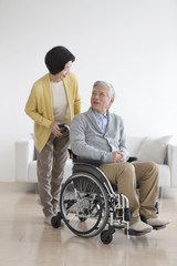 Senior man in wheelchair and senior woman