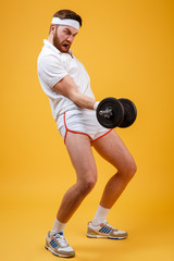 Vertical image of screaming sportsman doing exercise with dumbbell