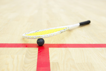 squash racket and ball on the court