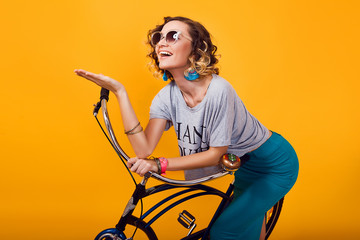 Young woman with retro bike standing in front of yellow background, sportive fit days, casual clothes, riding vintage bike, street fashion style, discover, emotions