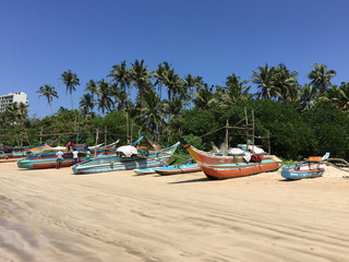 Local fishing boats lined along the beach at Weligama bay, Sri Lanka