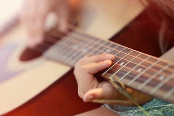 Girl playing guitar, closeup