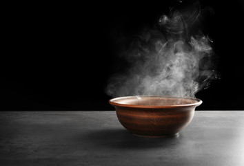 Ceramic bowl with hot liquid on table against dark background Wall mural