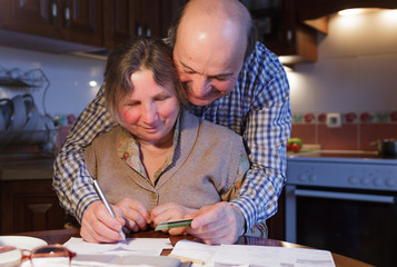 An elderly couple counting money and a budget.