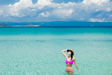 beautiful young woman standing in the wonderful clean sea in greece