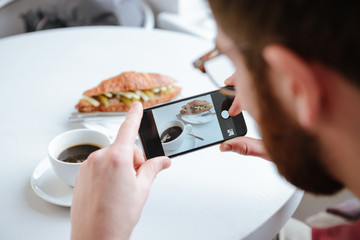 Side view of a man taking photo of his food in cafe