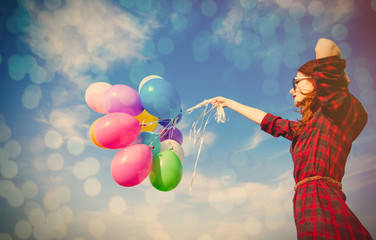 beautiful young woman with colorful balloons on the wonderful sky background