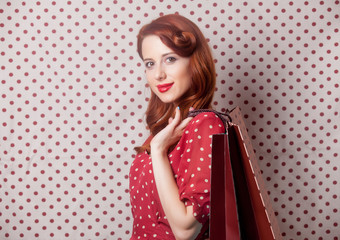 beautiful young woman with shopping bags  standing in front of the wonderful dotted background