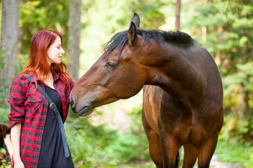 beautiful young woman touching wonderful horse on the natural forest background