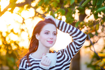 beautiful young woman with cup of coffee on the wonderful trees background
