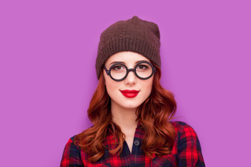 beautiful young woman standing in hipster glasses on the wonderful purple background