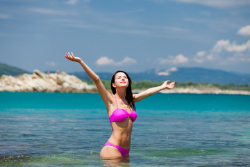 beautiful young woman standing in the clear and calm sea in sunny Greece