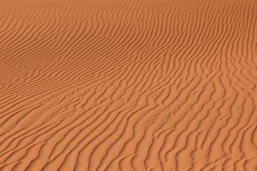 Rippled red brown desert or beach sand texture. Wavy background.
