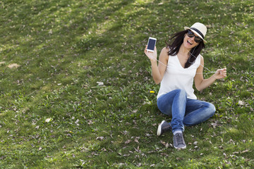 beautiful young woman listening to music on her smart phone. She is dancing and having fun outdoors.