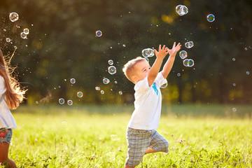 Male child catches soap bubbles in nature