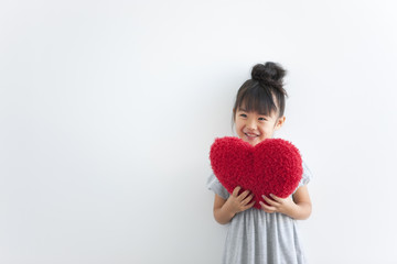 Girl holding red heart cushion, white background, copy space