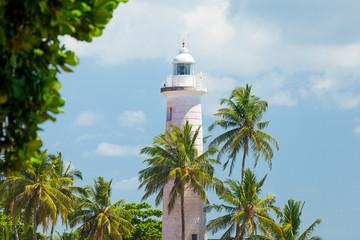 GALLE, SRI LANKA - JANUARY 26, 2016: beautiful lighthouse surrounded with palms on the wonderful sky background in Galle, Sri Lanka