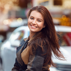 Close-up portrait of beautiful young adult woman with natural teeth smile looking at camera. Elegant brunette woman with hairstyle.