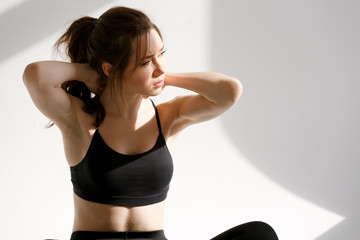 Portrait of a fitness woman sitting and having neck pain