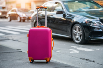 Luggage bag on the city street ready to pick by airport transfer taxy car. Wall mural