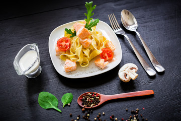 Pasta with salmon on dark background. Flat lay, top view. Restaurant, food