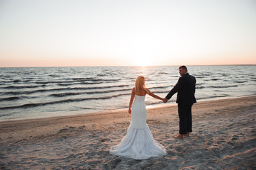 young couple stands at the sea beach looking at sunset