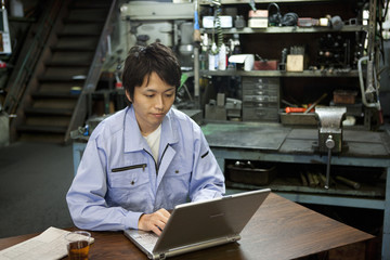 Male Factory Worker Using Laptop