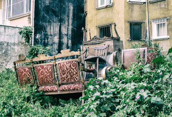 Old furniture abandoned in a green yard. Photo in vintage style.