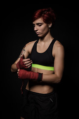 Woman is wrapping hands with red boxing wraps