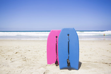 Two colorful boogie boards resting on a pristine beach. Ready to ride and have fun in the ocean on a clear summer day. Vacation time