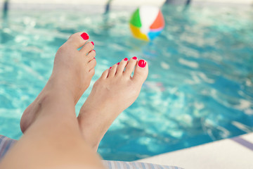 Beautiful sexy female feet relaxing by the swimming pool. Great pedicure photo.