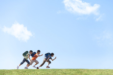 Schoolboys running at riverbank, copy space