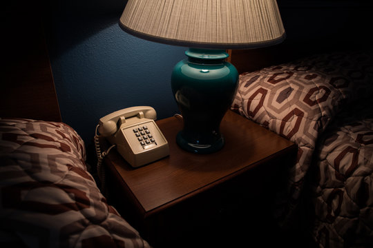 Old phone and lamp on a bedside table in a hotel room